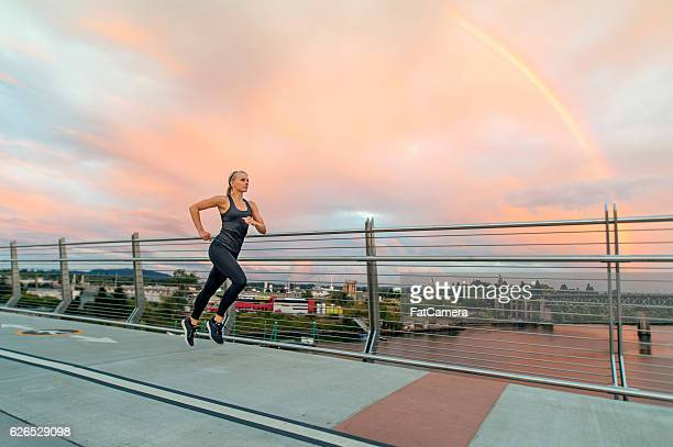 Athletic female running as the sun sets with a rainbow
