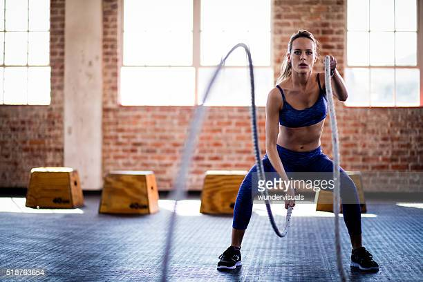 Athletic girl focused on fitness training with ropes at gym