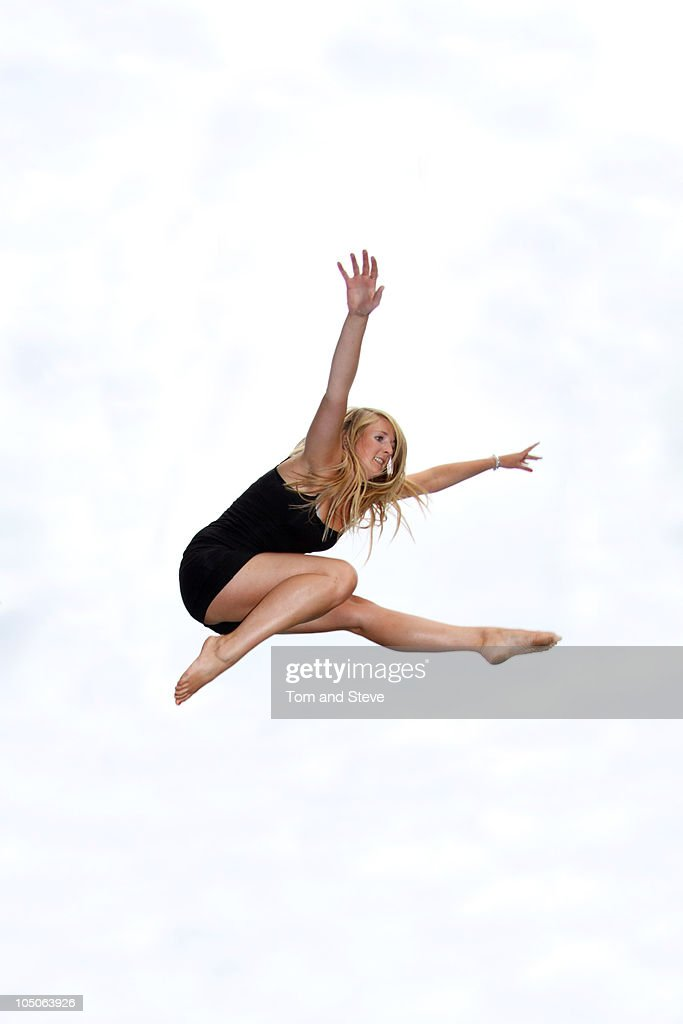 Athletic Girl poses mid-jump on trampoline : Stock Photo