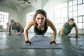Female leads gym power yoga group class strength determination drive as physical trainer instructor in push ups intense focused expression. Fitness exercise gym group muscle building workout with woma