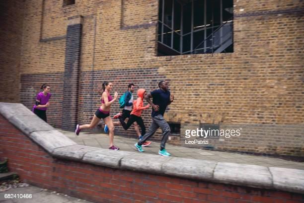 Athletic group of urban runner people exercising in London