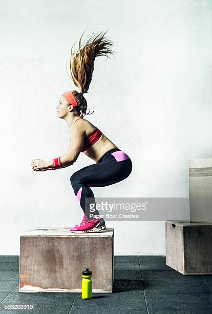 Athletic gym woman jumping on a wooden box