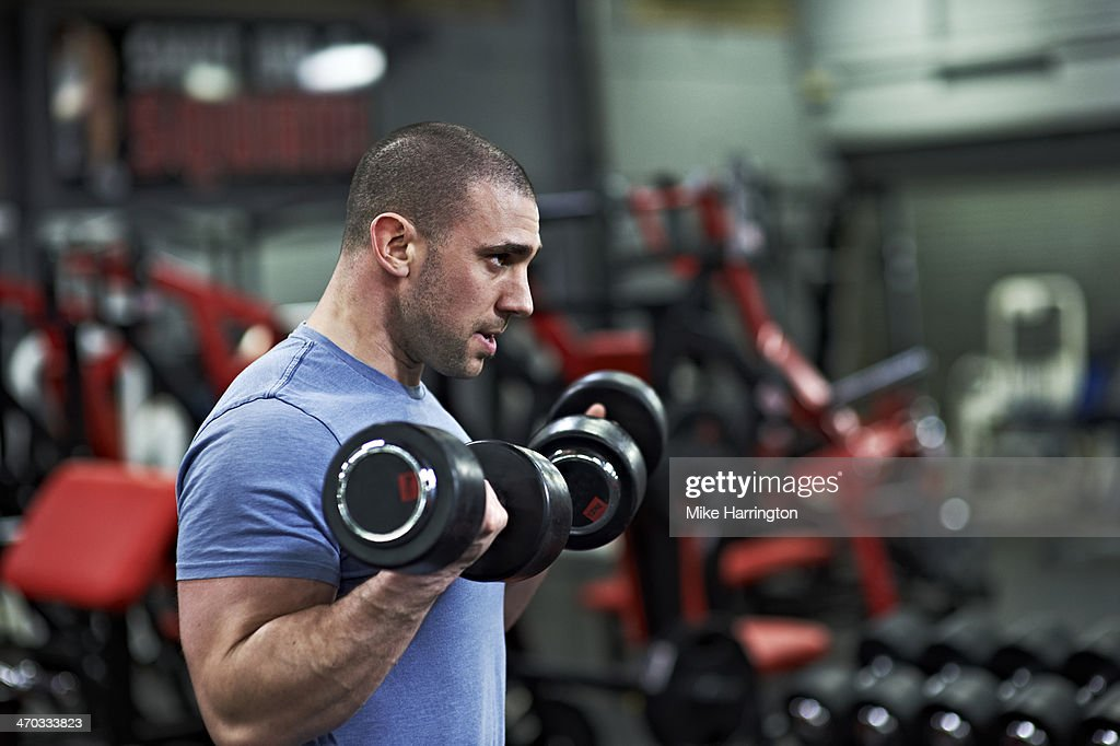 Athletic Male Lifting Dumbbells in Gym : Stock Photo
