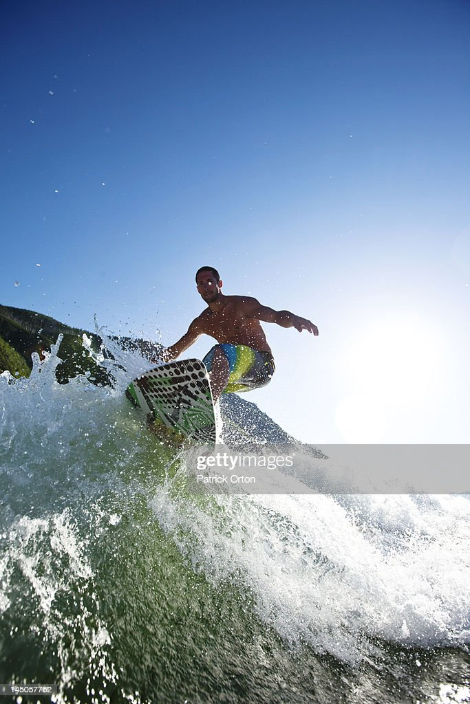 A athletic male surfing behind a wakeboard boat on a lake in Idaho. : Stock Photo