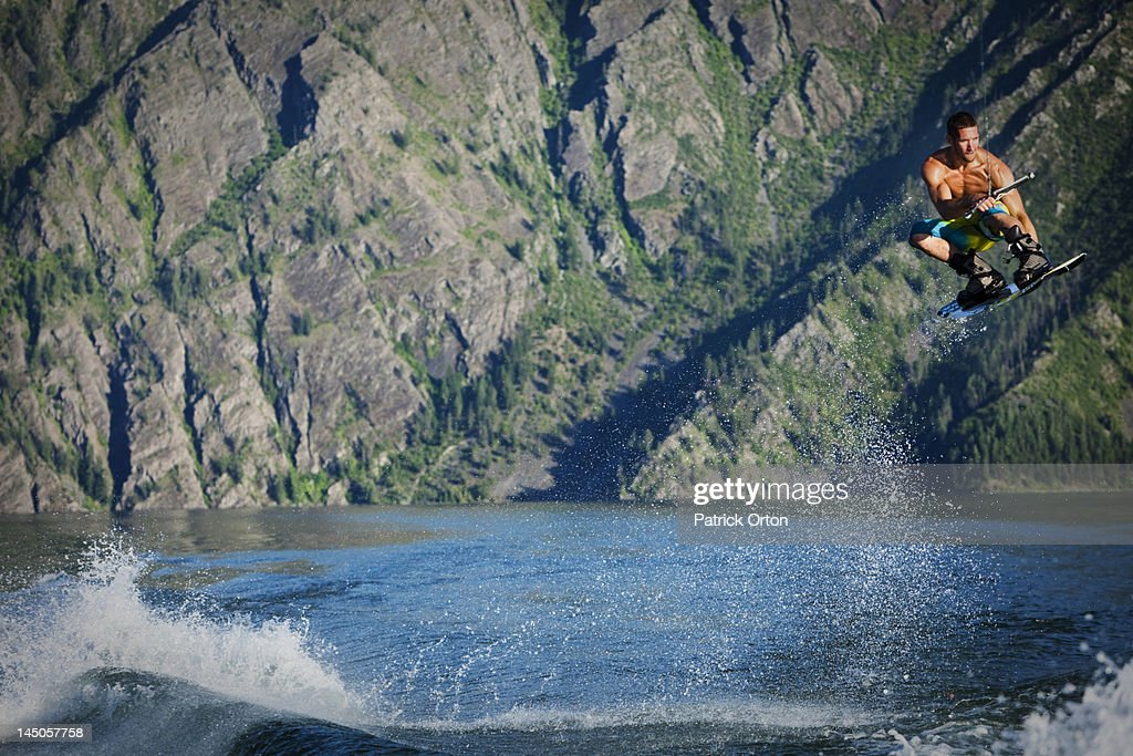 A athletic male wakeboarder boosts over the wake at sunset on a lake in Idaho. : Stock Photo