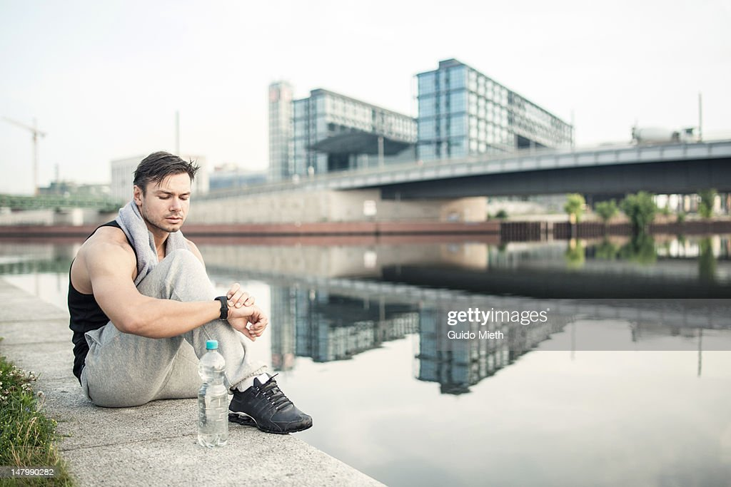 Athletic man checking his health monitor bracelet : Stock Photo