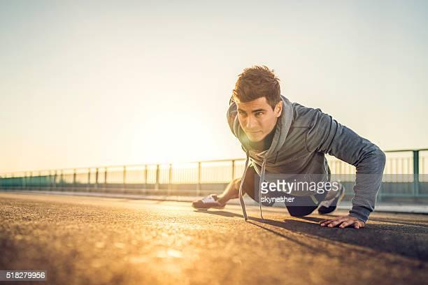 Atlético homem fazendo push-up em uma estrada ao pôr do sol.