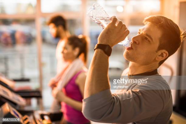 Athletic man drinking water in a health club.