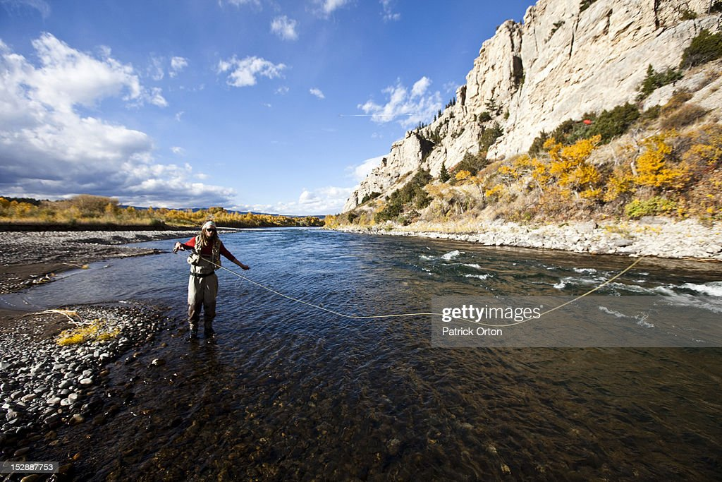 A athletic man fly fishing stands in a river with the fall colors and snowy mountains behind him.