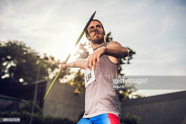 Athletic man on competition ready to throw a javelin.