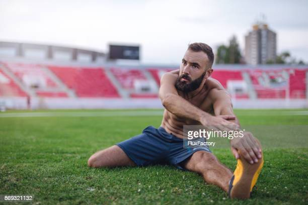 Athletic man stretching legs