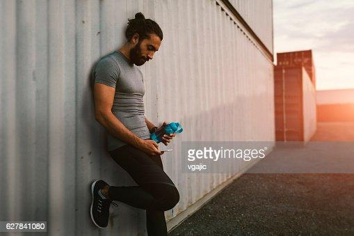 Athletic Man Using His Smart Phone.