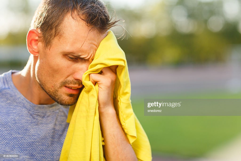 Athletic man wipes his face with yellow towel : Stock Photo
