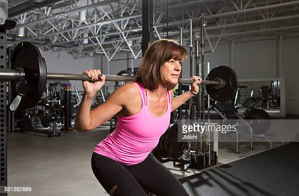 Athletic Mid Adult Woman Doing a Weightlifting Workout.