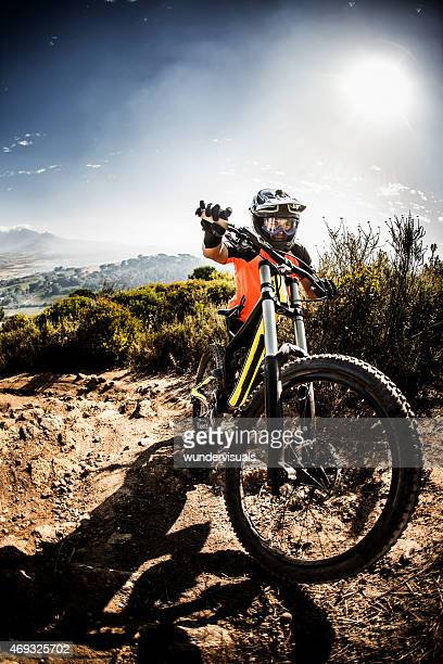 Athletic mountain biker pushing his bike up a dirt path