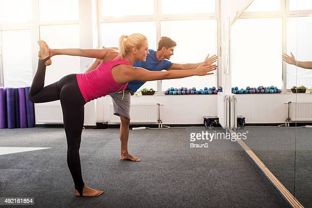 Athletic people doing balance exercises in good posture.
