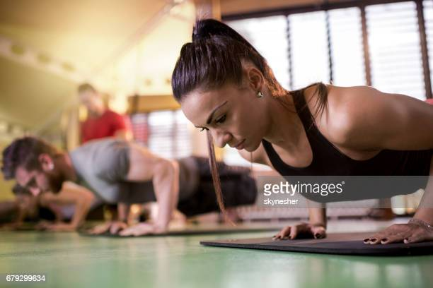 Athletic people doing push-ups on a sports training in a health club.