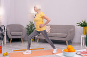 Enjoy dynamic exercises. Slim elderly woman doing morning calisthenics in the living room and performing lunges