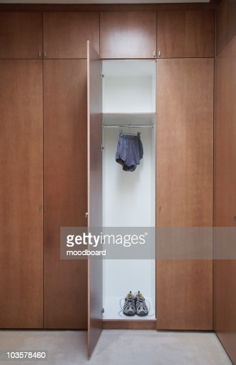 Athletic shoes and running shorts in locker with open door