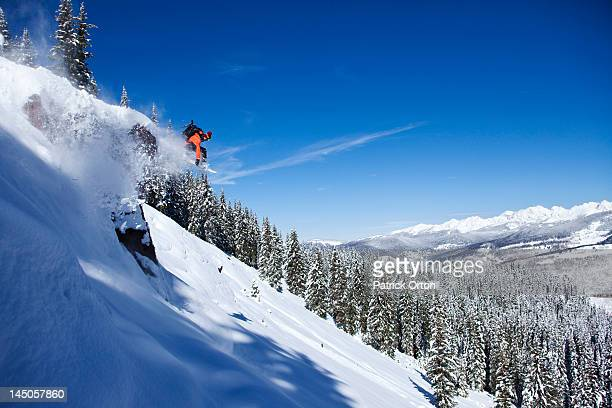 A athletic snowboarder jumping off a cliff on a sunny powder day in Colorado.