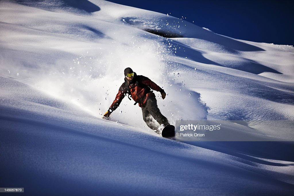 A athletic snowboarder rips fresh powder turns in the backcountry on a sunny day in Colorado.