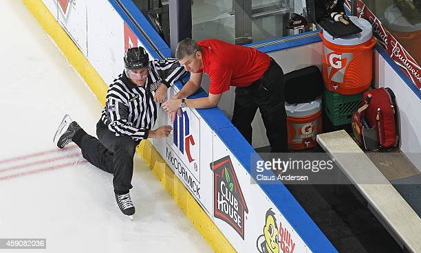 Athletic Therapist Andy Brown of the Owen Sound Attack chats with linseman Kevin Hastings prior to play against the London Knights in an OHL game at...