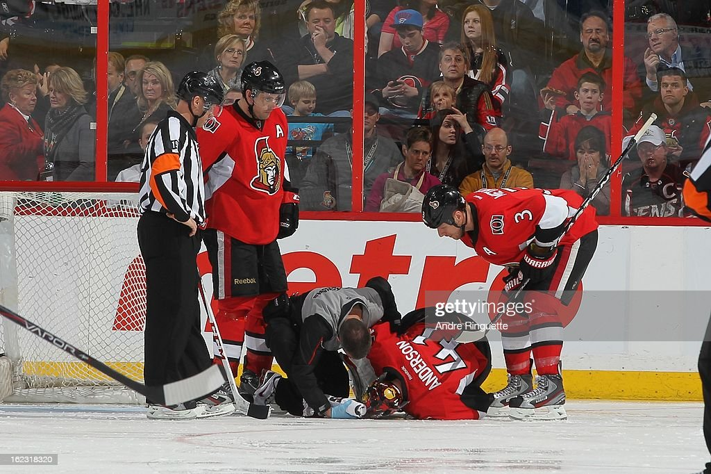 Athletic therapist Gerry Townend attends to Craig Anderson #41of the Ottawa Senators after being injured in the third period of an NHL game against the New York Rangers as teammates Chris Phillips #4 and Marc Methot #3 look on on February 21, 2013 at Scotiabank Place in Ottawa, Ontario, Canada.