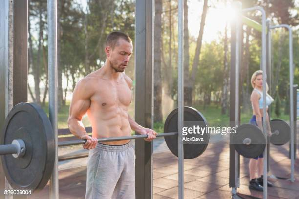 Athletic topless man lifting dumbbell outdoor in the park