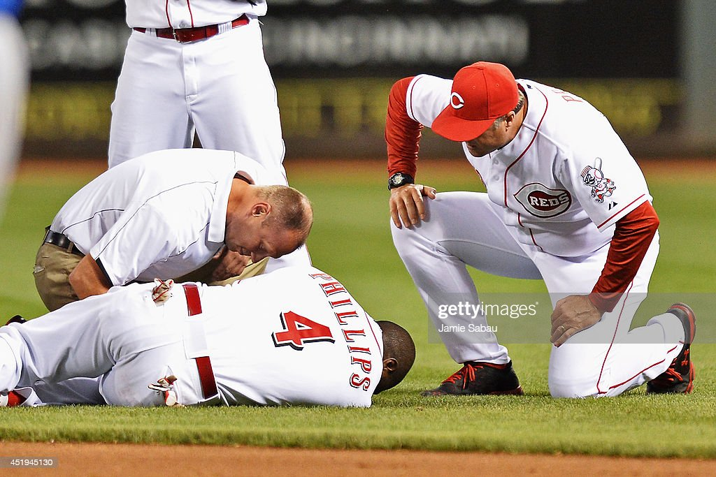 Athletic trainer Steve Baumann of the Cincinnati Reds attends to Brandon Phillips #4 of the Cincinnati Reds and Manager <a gi-track='captionPersonalityLinkClicked' href=/galleries/search?phrase=Bryan+Price&family=editorial&specificpeople=762918 ng-click='$event.stopPropagation()'>Bryan Price</a> #38 of the Cincinnati Reds watches after Phillips injured his thumb diving for a ball in the eighth inning against the Chicago Cubs at Great American Ball Park on July 9, 2014 in Cincinnati, Ohio. Cincinnati defeated Chicago 4-1.