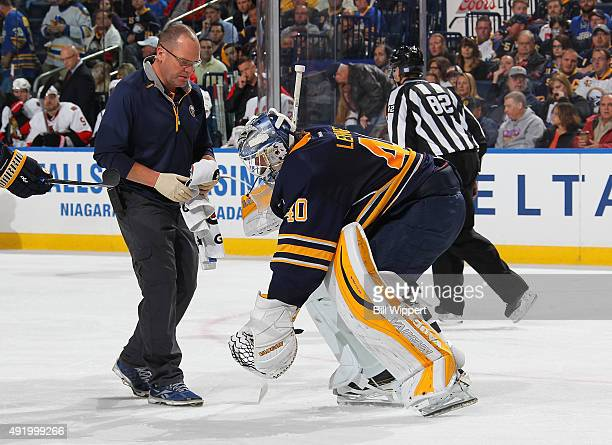 Athletic trainer Tim Macre watches as goaltender Robin Lehner of the Buffalo Sabres reacts to an injury in a game against the Ottawa Senators on...
