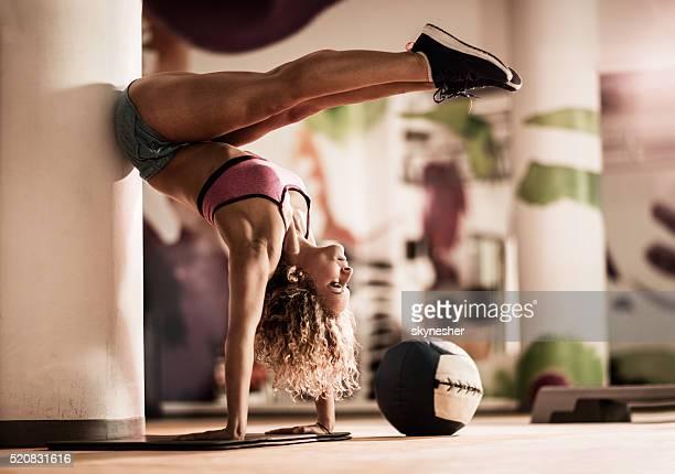 Sportive femme en équilibre sur les mains dans un Club de remise en forme.