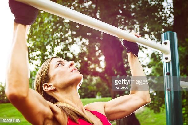 Sportliche Frau tun Pull-Ups an einem sonnigen Tag