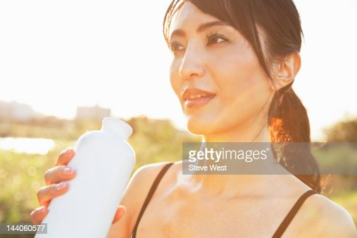 Athletic woman drinking from water bottle : Stock Photo