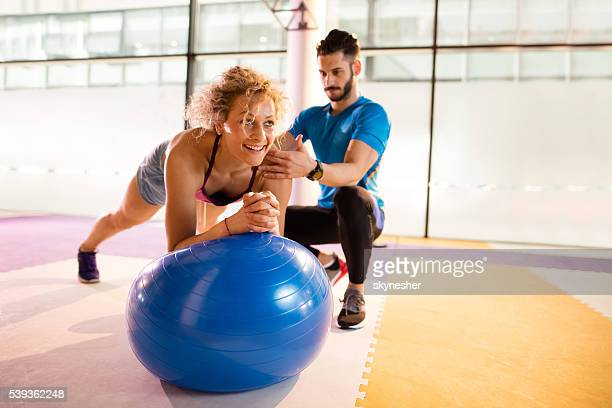 Athletic woman having Pilates training with fitness instructor.