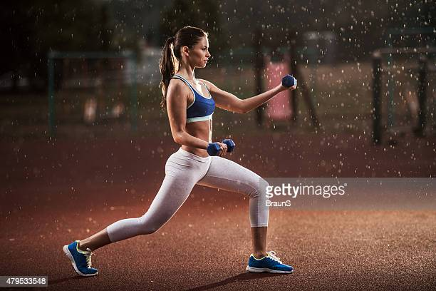 Athletic woman having weight training on a rain.