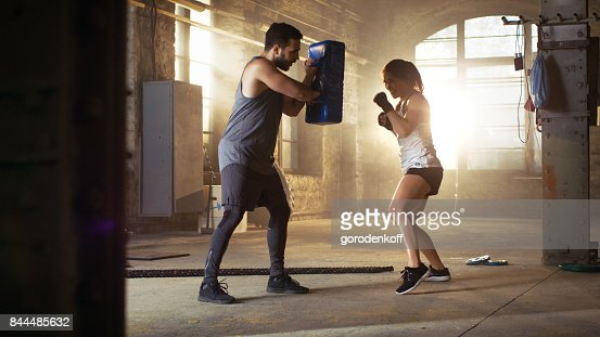 Athletic Woman Hits Punching Bag that Her Partner/ Trainer Holds. She's Professional Fighter and is Training in a Gym. : Stock Photo