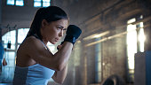 Athletic Woman is ready for Punch Punching Bag. She's Strong and Gorgeous Woman. They Workout in a Gym.