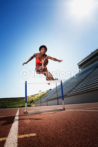 Athletic Woman Jumping Over Hurdle Stock Photo