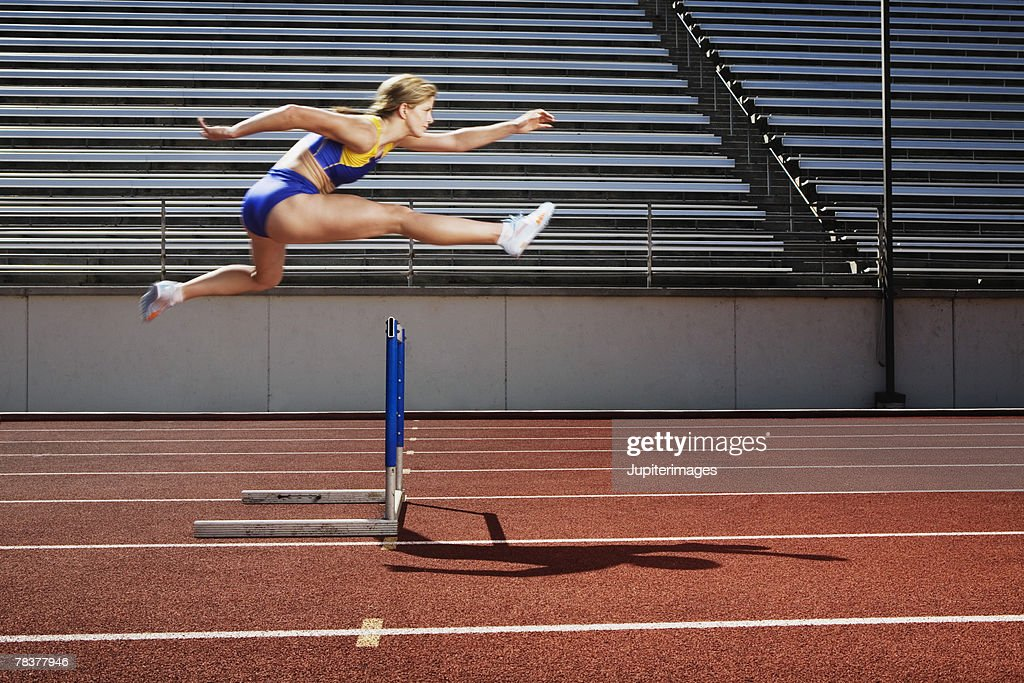 Athletic woman jumping over hurdle : Stock Photo