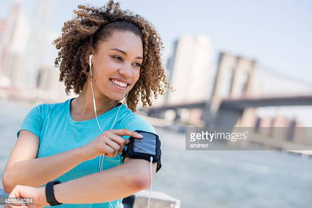 Athletic woman listening to music while working out outdoors