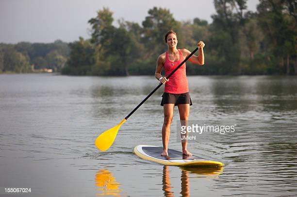 Femme athlétique à rame sur un lac calme du Midwest américain.
