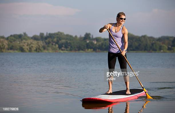 Athletic Woman Paddle Boarding on a Calm Midwestern Lake.
