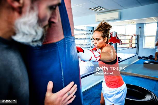 Athletic woman punching a bag in gym
