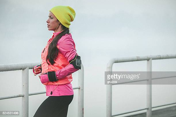Athletic woman running and listening music in the city port