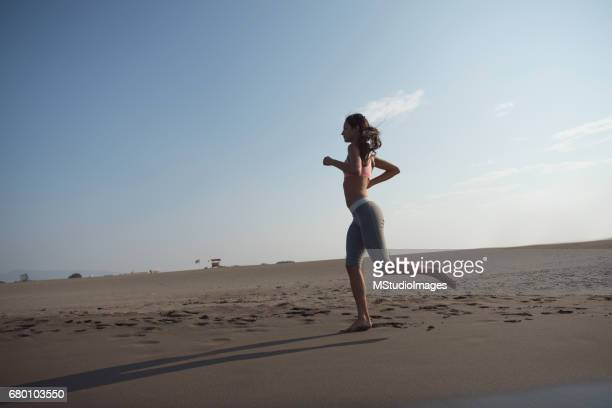 Athletic woman running at the beach.