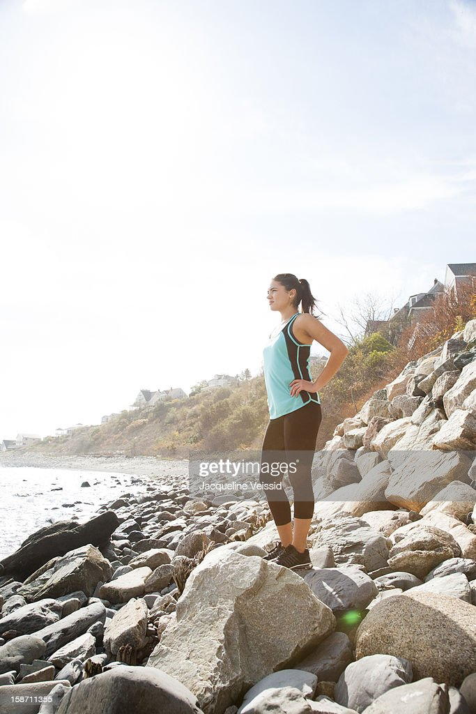 Athletic woman standing on rocky beach : Stock Photo