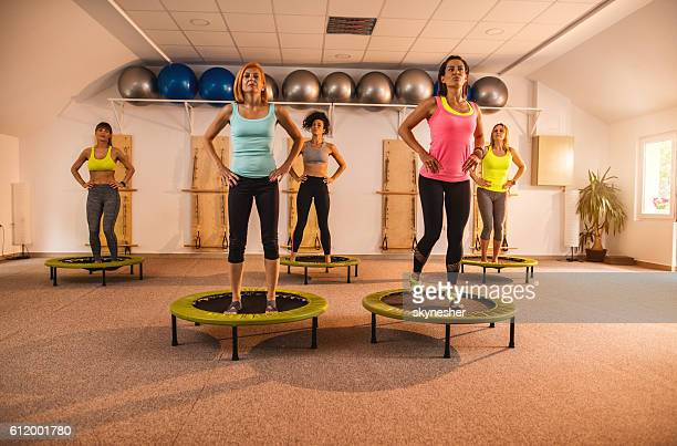 Athletic women exercising on mini trampolines in health club.
