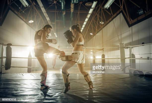 Athletic women fighting on a boxing match in a gym.