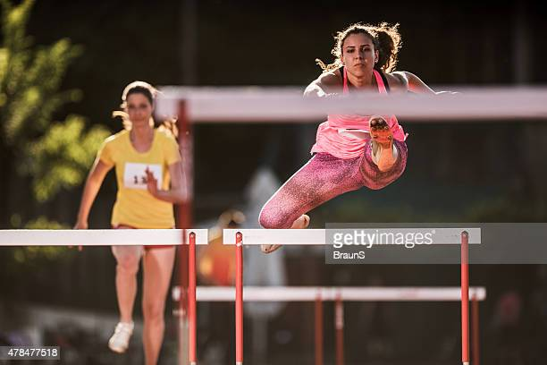 Athletic women hurdling on a sports race.