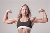 Bodyfitness model training biceps. High resolution studio snapshot. Soft light stylish image. Half-lenght portrait.